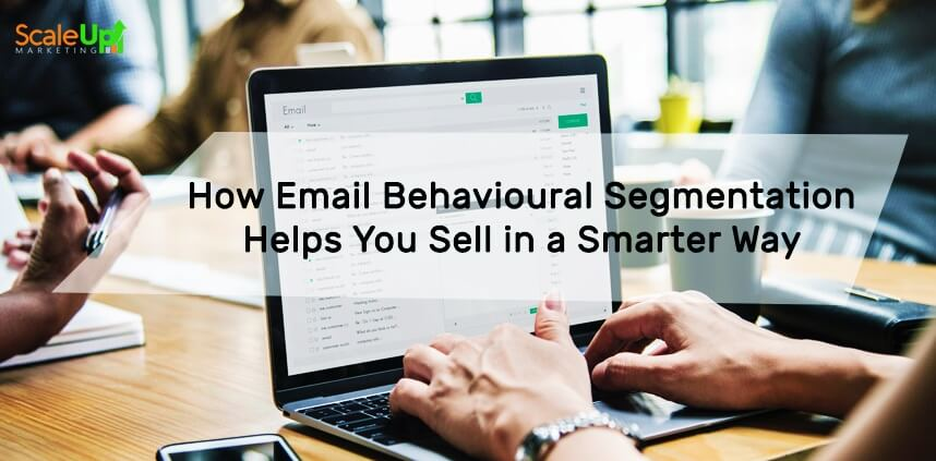 """header image of the blog title """"How Email Behavioural Segmentation Helps You Sell in a Smarter Way"""" with an over-the-shoulder shot of a person typing on a laptop and a background of people sitting in front a wooden table"""