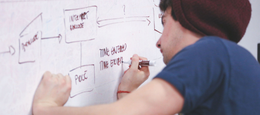 a guy wearing a blue shirt and red bonnet writing on a whiteboard using his right hand, this is an example of creating a database using marketing automation
