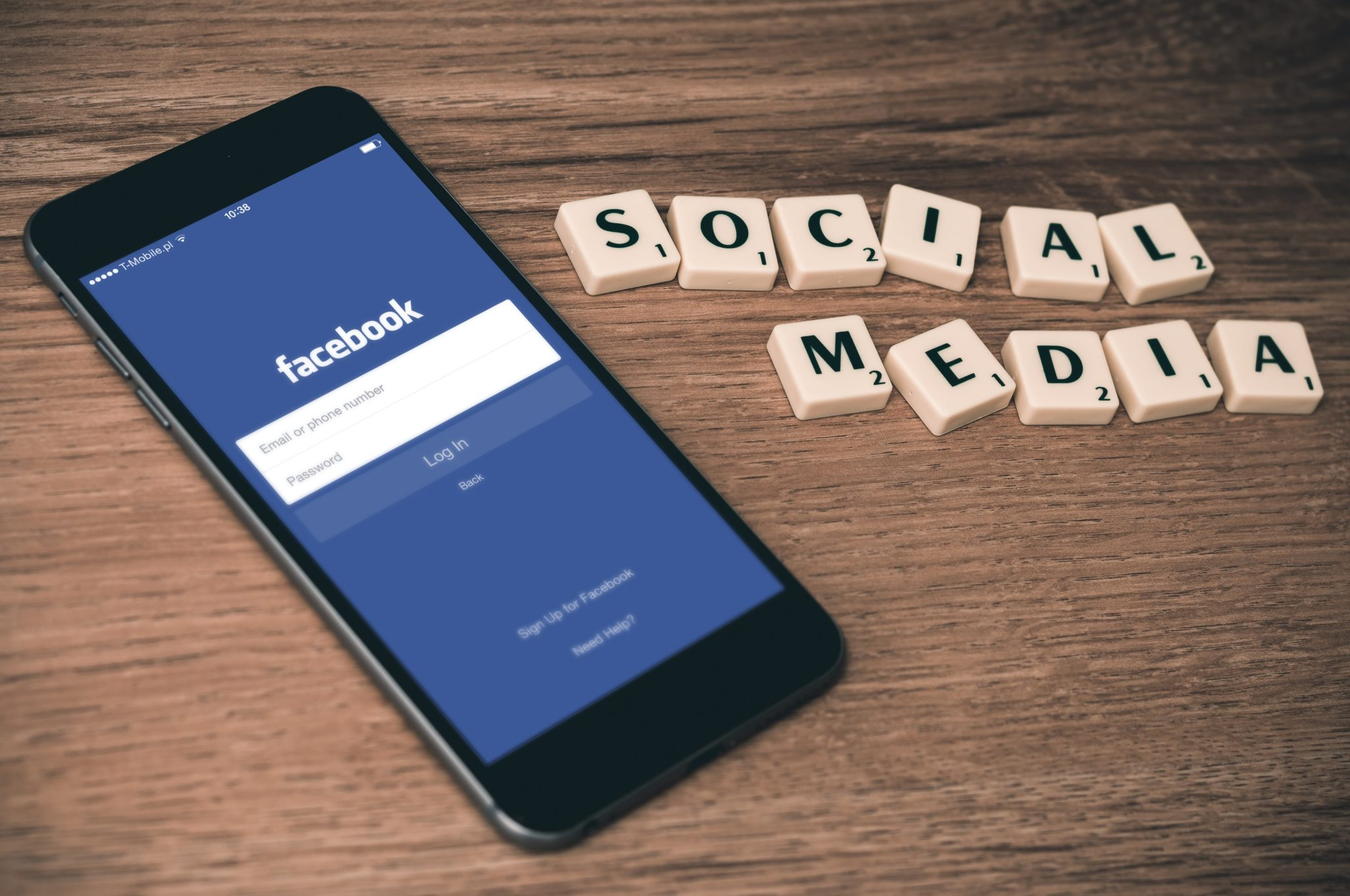 """An open cellphone on the table with facebook login on the screen with word tiles that indicate """"social media"""" letters on the side, this is an example of marketing automation platforms."""