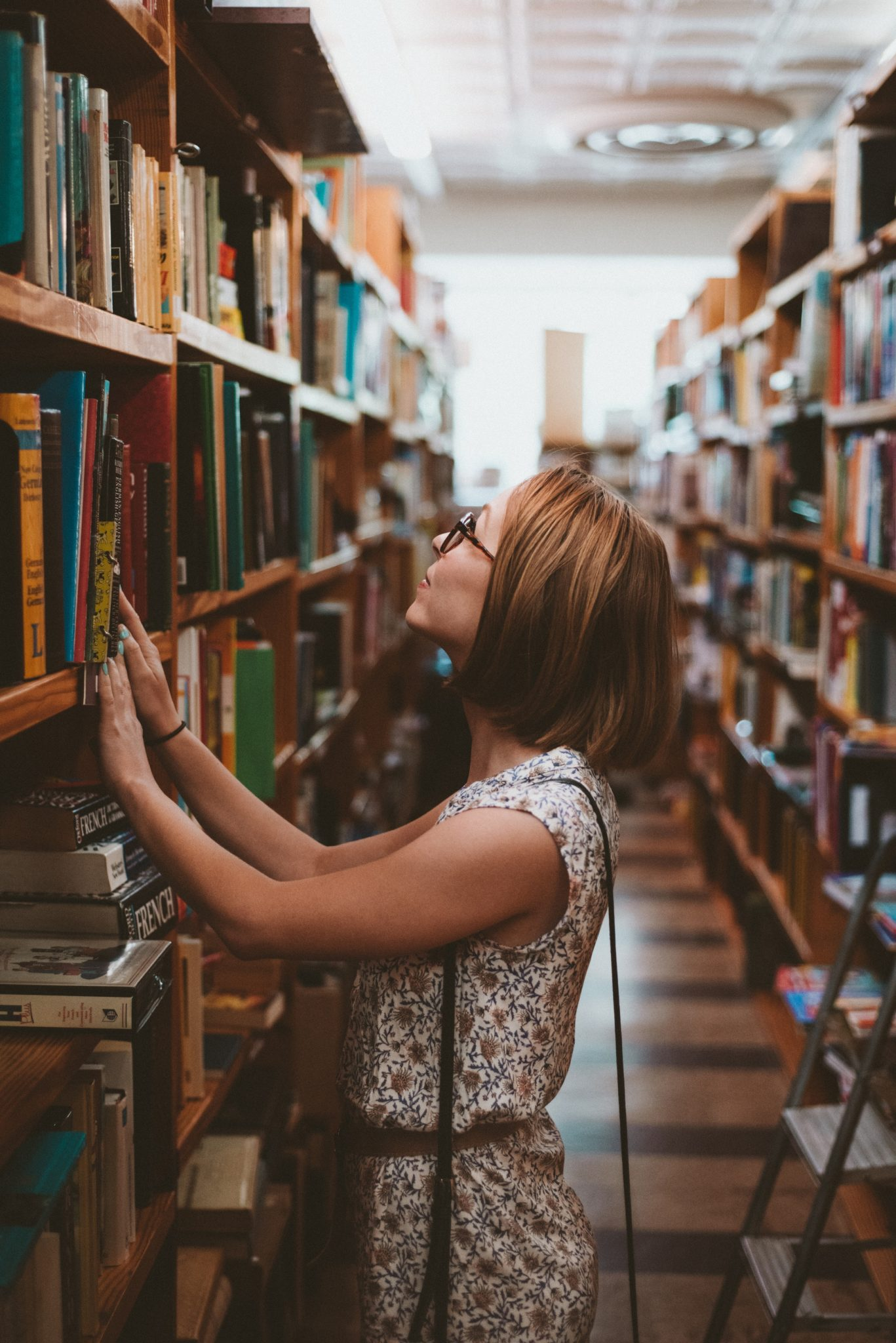 A woman standing in a library holding her hands in a bookshelf,searching for a book, is an example of lead nurturing programs for education of an effective campaign.