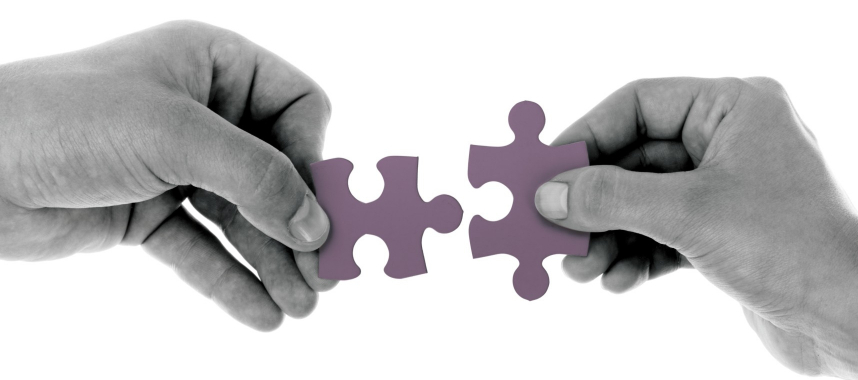 2(two) black and white hands trying to connect 2(two) pink puzzle pieces, this is an example of getting connected to audience under the topic marketing across multiple channels