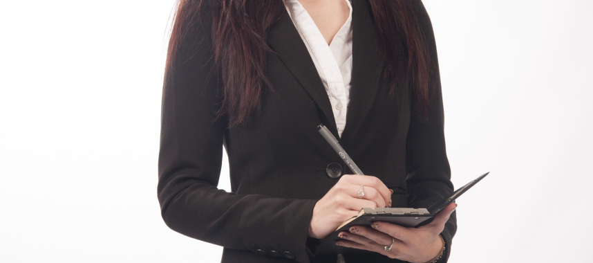 a torso of a woman wearing corporate attire holding and writing on the notebook on her left hand, this is an example of managing customers under the topic muti-channel marketing