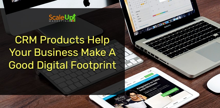 """header image of the blog title """"CRM Products Help Your Business Make A Good Digital Footprint"""" with a close-up shot of a personal computer, laptop and tablet on a wooden table"""