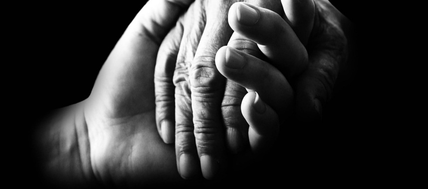 black and white image of a person's hand holding another hand passionately, this is an example of empathy traits crm team should have
