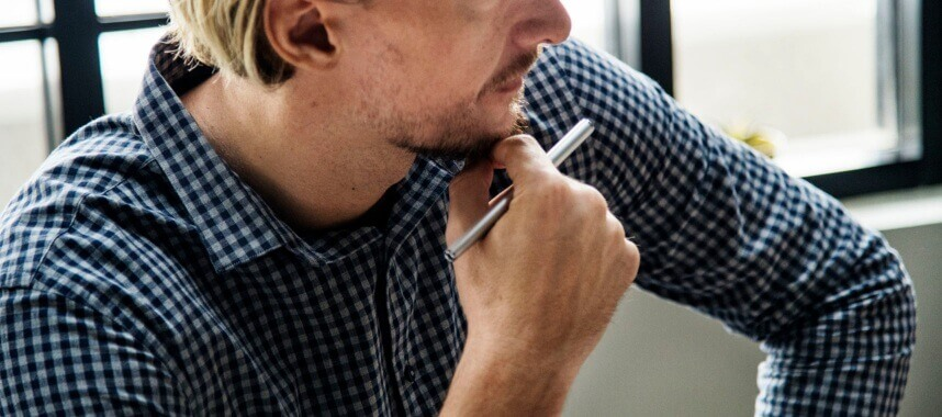 close-up shot of a guy holding a pen in his right hand while holding his chin thinking