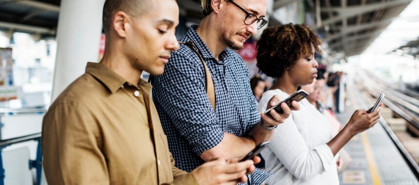 3 persons looking and holding each of their cellphones on a train station
