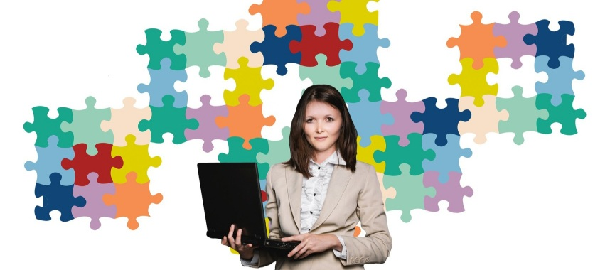 a woman facing in front wearing a corporate attire and holding a laptop with colorful puzzle pieces in the background