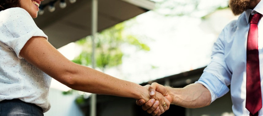 two persons smiling while shaking hands