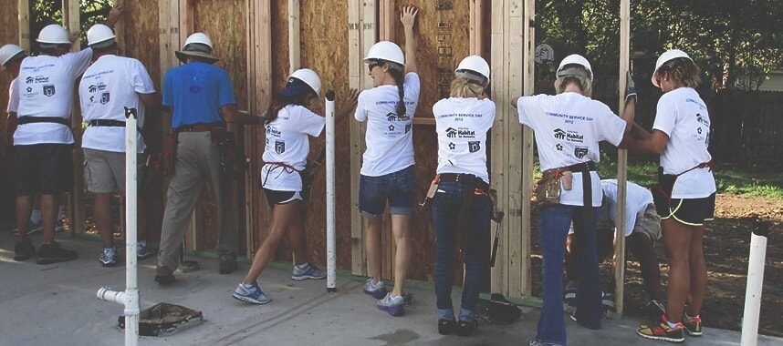 people wearing white shirt and helping each other to build a wooden wall