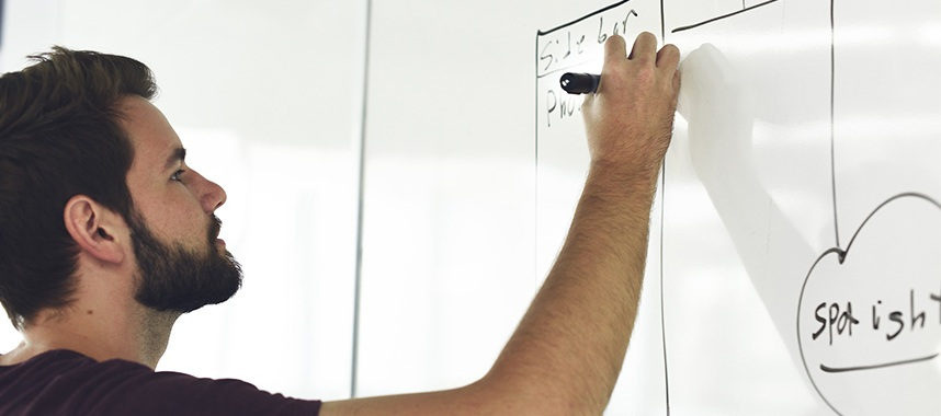 a bearded guy writing on a whiteboard using a black marker