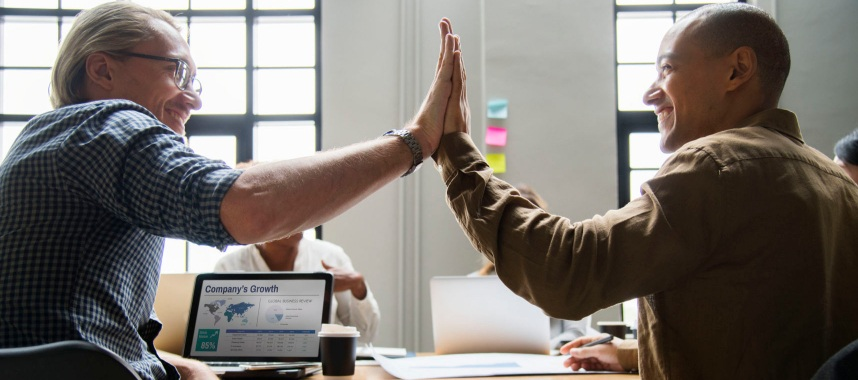 2 happy persons in a room doing the high-five sign with laptops, papers and coffee on a wooden surface, this is one of the example for an effective referral marketing strategy