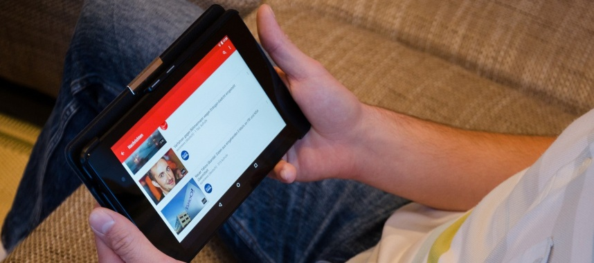 a person sitting on a couch watching youtube videos on a black tablet, youtube is one of the example of social media sites to get repeat customers