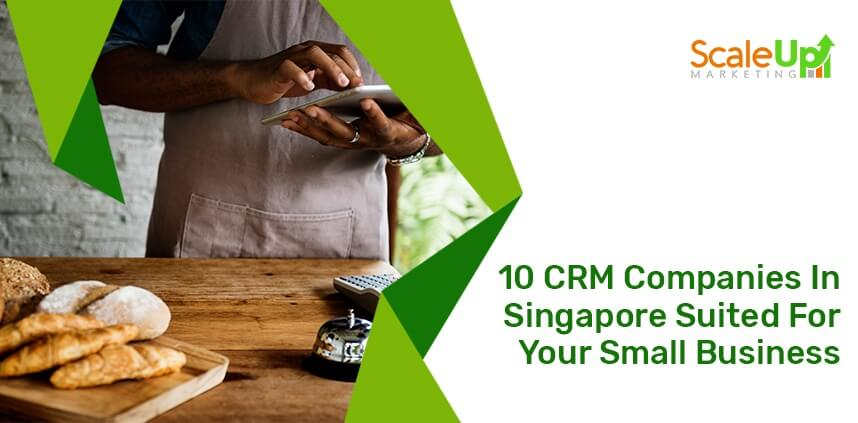 """header image of the blog title """"10 CRM Companies In Singapore Suited For Your Small Business"""" with a background of a baker operating a tablet in front of a wooden table"""