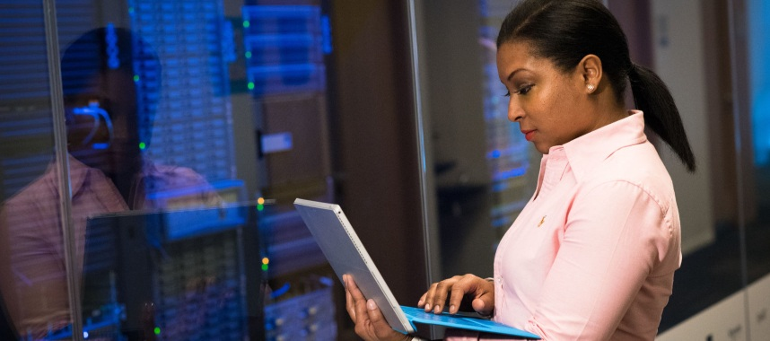 a standing woman wearing a pink polo while holding a laptop in front a server, this is an example of server crm system