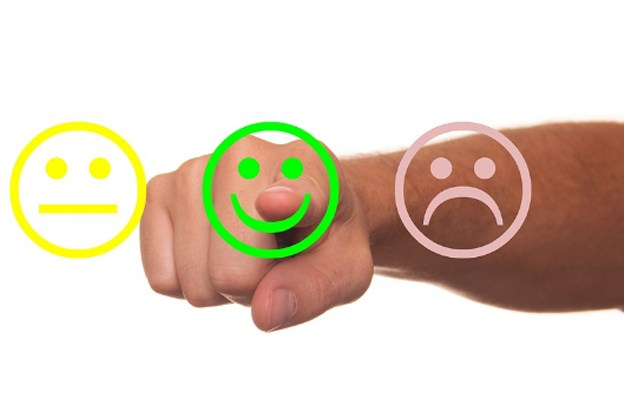 3 emoticon faces ``Not interested``, ``Happy``, and ``Sad`` with a right hand pointing directly to a green happy emoticon