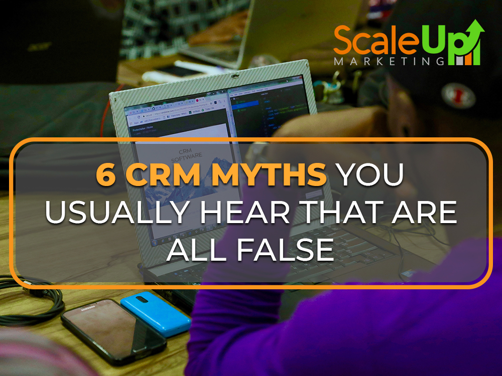 "blog title""6 CRM Myths You Usually Hear That Are All False"" a header with a background of a man wearing violet longsleeve in front of a laptop with two cellphones on a wooden table"